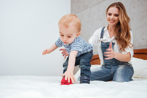 Happy young mother playing with her little son on bed at home