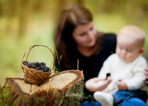 Happy young mother spending time with her baby son in forest picking and eating berries. Focus on the basket with berries