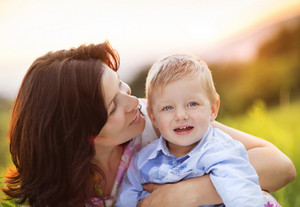 Happy young mother with her little son have fun together in nature in sunset field