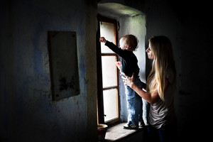 Happy young mother with her son in old house
