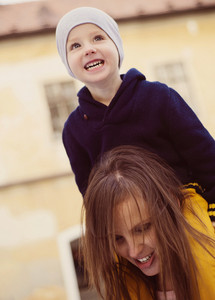 Happy young mother with her son on a walk in an autumn city