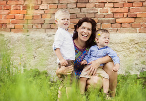 Happy young mother with her two little sons have fun together in nature by the old brick house
