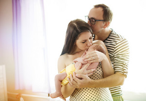 Happy young parents with their newborn baby girl at home