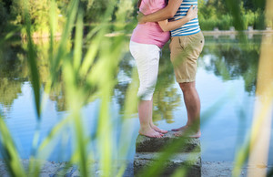 Happy young pregnant couple hugging by the lake