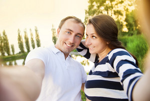 Happy young pregnant couple hugging in nature and taking selfie