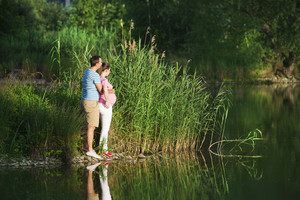 Happy young pregnant couple hugging in nature, reflecting in the lake