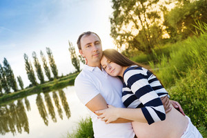 Happy young pregnant couple hugging in nature