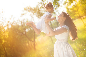 Happy young pregnant mother and her little daughter have fun in summer nature