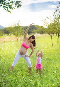 Happy young pregnant mother exercising with her little daughter in summer nature