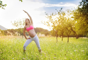 Happy young pregnant woman exercising in summer nature