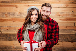 Happy young smiling couple in winter wear standing and holding gift box isolated on wooden background
