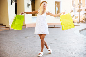 Happy young smiling woman in hat holding shopping bags while walking on the street