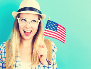 Happy young traveling woman holding American flag on blue background