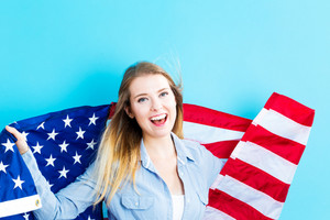 Happy young traveling woman holding American flag