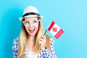 Happy young traveling woman holding Canadian flag