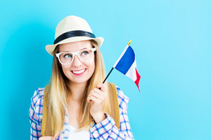 Happy young traveling woman holding French flag