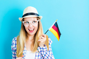 Happy young traveling woman holding German flag