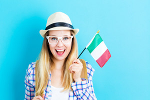 Happy young traveling woman holding Italian flag