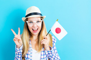 Happy young traveling woman holding Japanese flag on blue background