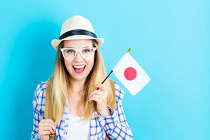 Happy young traveling woman holding Japanese flag