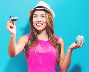 Happy young traveling woman on a blue background