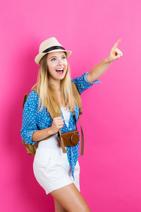 Happy young traveling woman on a pink background