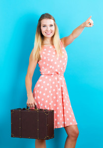 Happy young traveling woman on blue background