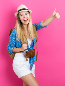 Happy young traveling woman on pink background
