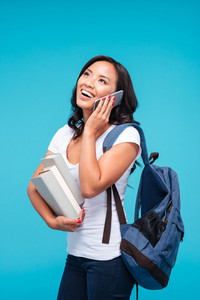 Happy young vietnamese girl holding backpack and books talking on the phone isolated on a blue background