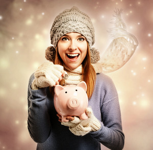 Happy young woman depositing money into her pink piggy bank