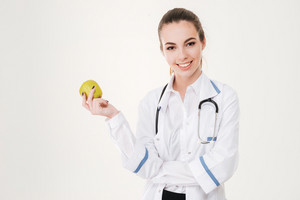 Happy young woman doctor smiling and holding an apple over white background