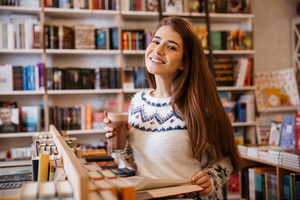 Happy young woman drinking coffee and reading boo indoors