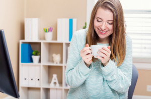 Happy young woman drinking coffee at a desk in her home office