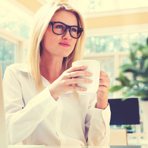 Happy young woman drinking coffee in an office