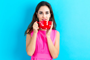 Happy young woman drinking coffee on a blue background