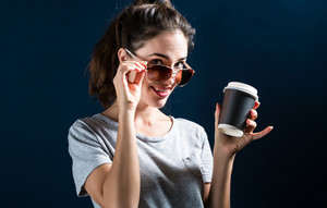 Happy young woman drinking coffee on a dark blue background
