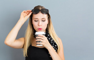 Happy young woman drinking coffee on a gray background