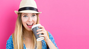 Happy young woman drinking coffee on a pink background
