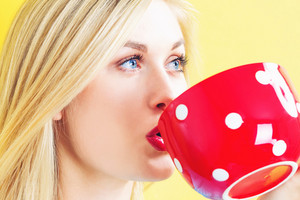 Happy young woman drinking coffee on a yellow background