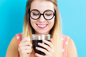 Happy young woman drinking coffee on blue background