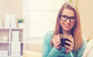 Happy young woman drinking coffee on her couch at home