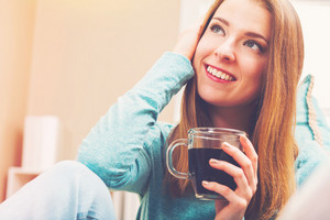Happy young woman drinking coffee on her couch