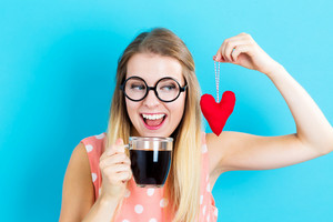 Happy young woman drinking coffee with a heart cushion