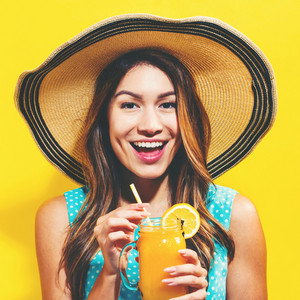 Happy young woman drinking smoothie on a yellow background