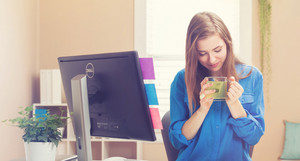 Happy young woman drinking tea in her home office