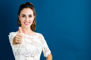 Happy young woman giving a thumb up on a dark blue background