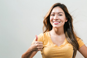Happy young woman giving a thumb up on a pink background