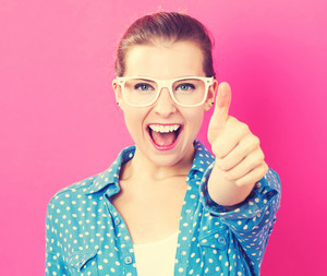 Happy young woman giving a thumb up on pink background