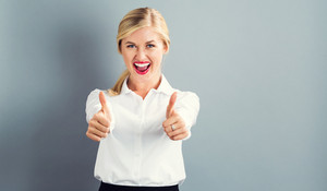 Happy young woman giving a thumbs up on a gray background