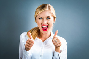 Happy young woman giving thumbs up on a gray background